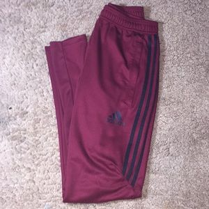 Burgundy adidas pants.